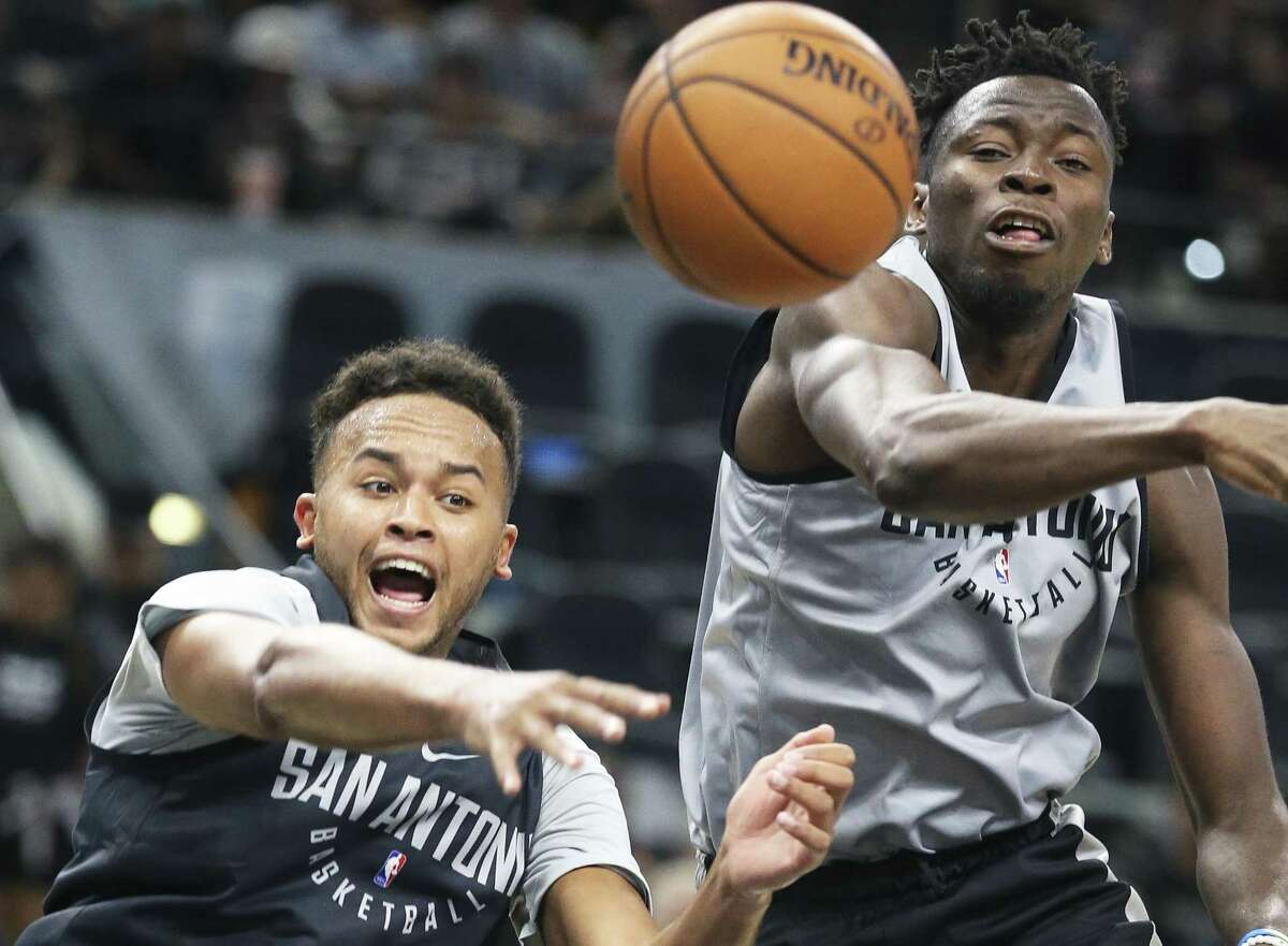 Kyle Anderson (left) throws a pass to the corner past Amida Brimah during the Spurs' Silver& Black intrasquad scrimmage at the AT&T Center on Sept. 30, 2017.