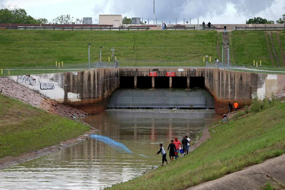 A man throws a net into Buffalo Bayou with the Barker Dam and Barker Reservoir in the background.. ( Gary Coronado / Houston Chronicle ) Photo: Gary Coronado, Staff / Internal