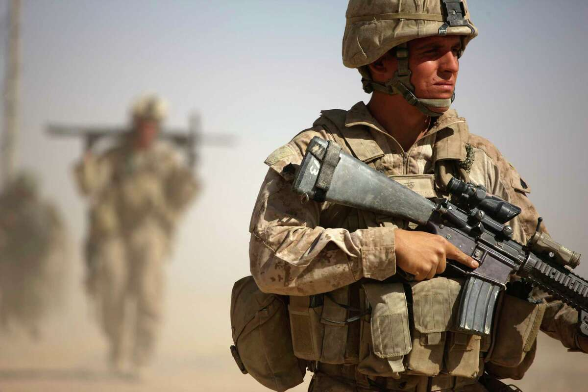 A U.S. Marine, right, with Bravo Company, 1st Battalion 5th Marines walks in a joint patrol with Afghan National Army soldiers, in Nawa district, Helmand province, southern Afghanistan, Saturday, Oct. 3, 2009. (AP Photo/Brennan Linsley)