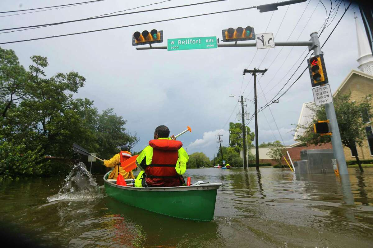 Houston fire fighters use a borrowed canoe to search for evacuees during extreme flooding in Meyerland, Sunday, Aug. 27, 2017, in Houston.