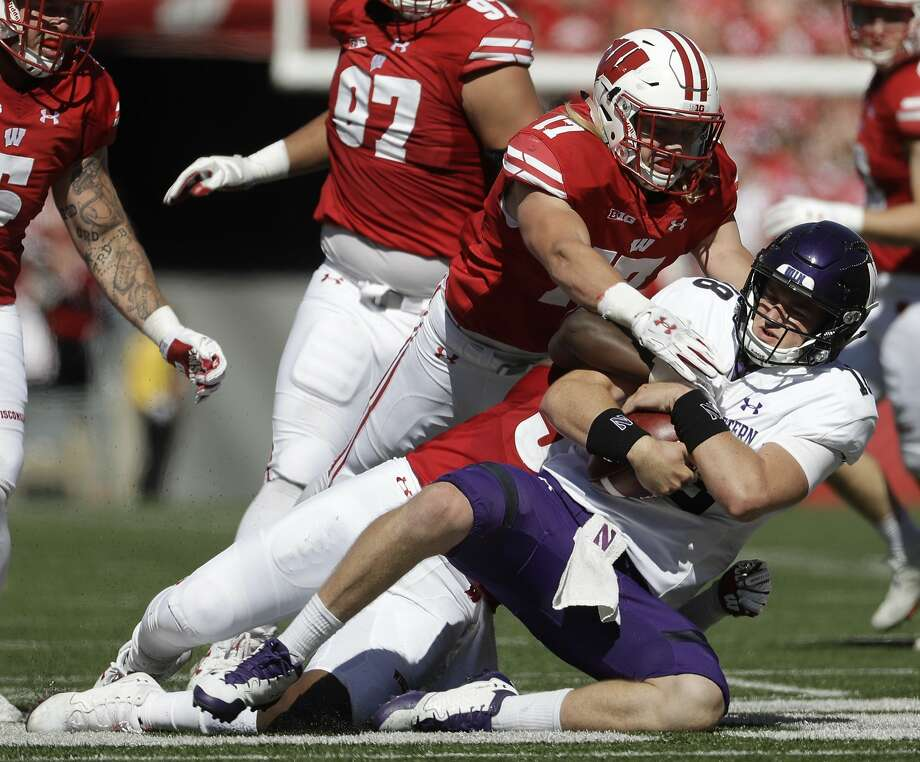 Northwestern's Clayton Thorson is sacked by Wisconsin's Andrew Van Ginkel as the No. 10 Badgers' vaunted defense turned in another dominating performance. Photo: Morry Gash, Associated Press