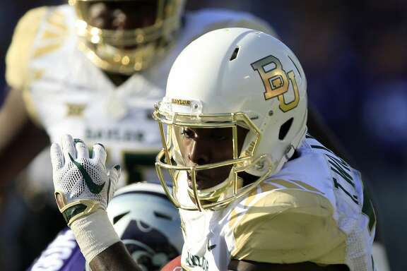 Baylor running back Terence Williams (22) gets past Kansas State defensive end Tanner Wood (34) during the second half of an NCAA college football game in Manhattan, Kan., Saturday, Sept. 30, 2017. (AP Photo/Orlin Wagner)