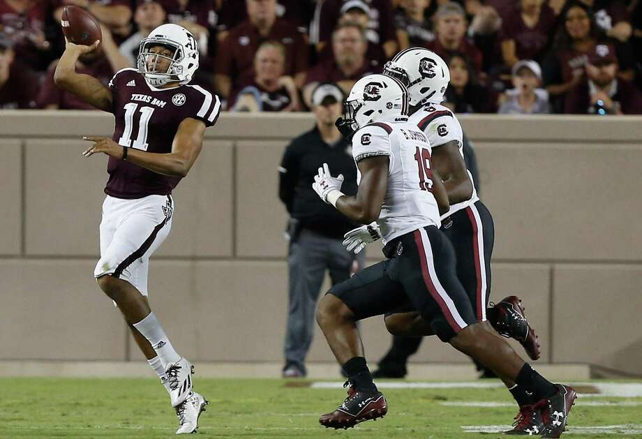 Kellen Mond #11 of the Texas A&M Aggies throws on the run as Brad Johnson #19 of the South Carolina Gamecocks and T.J. Brunson #6 apply pressure at Kyle Field on September 30, 2017 in College Station, Texas. Photo: Bob Levey /Getty Images / 2017 Getty Images