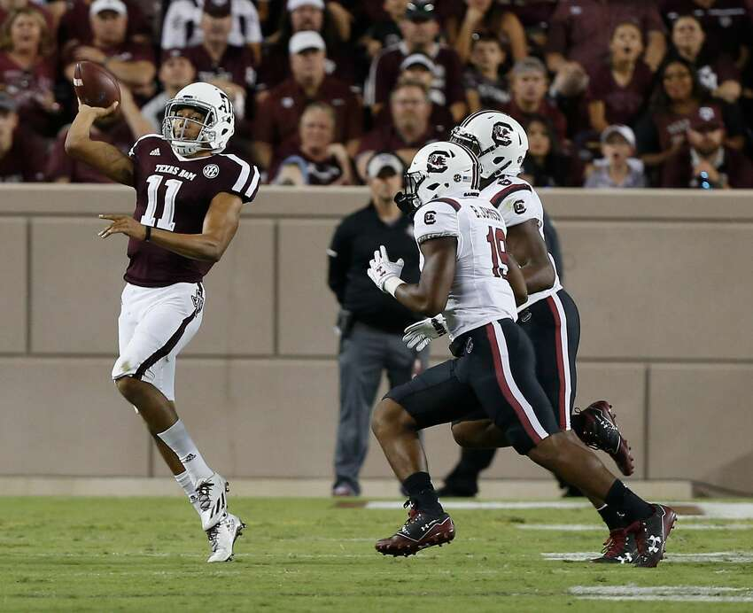 COLLEGE STATION, TX - SEPTEMBER 30: Kellen Mond #11 of the Texas A&M Aggies throws on the run as Brad Johnson #19 of the South Carolina Gamecocks and T.J. Brunson #6 apply pressure at Kyle Field on September 30, 2017 in College Station, Texas. (Photo by Bob Levey/Getty Images)