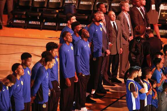 The Warriors stand, as usual, during the national anthem before their game against the Denver Nuggets at Oracle Arena.