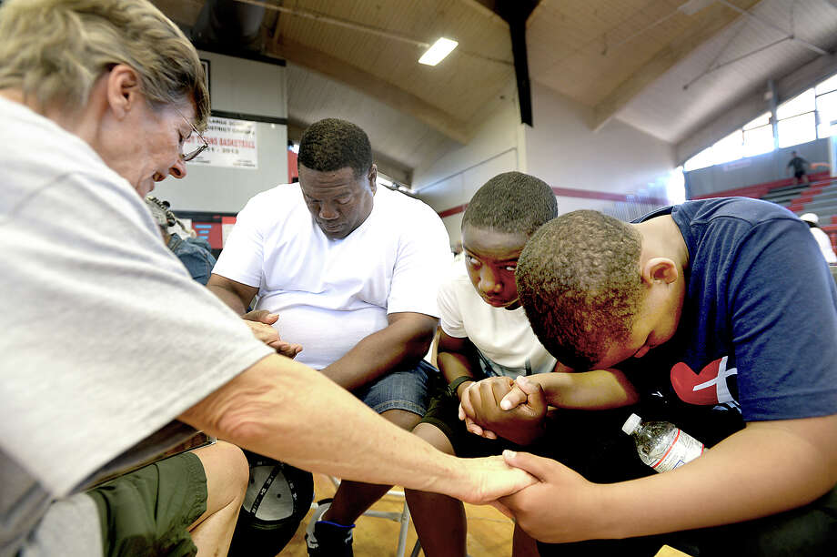 "Austin Disaster Relief Network volunteer Gloria Bell gathers with (from left) Dexter Antoine, Braelon Limbrick, and Clayton Harrison in a moment of prayer for strength and hope during the ""Love Port Arthur"" assistance program Saturday in Port Arthur. 1,000 volunteers from the faith-based organization traveled to the city, setting up a number of resource stations throughout the Thomas Jefferson Middle School campus. Their goal is to reach 10,000 residents in need of help rebuilding their homes and lives in the wake of Tropical Storm Harvey. Volunteers met with families throughout the day-long event, gathering information on their status and needs. Other stations offered pre-paid Visa cars, a ""thrift store"" with tables full of clothes, accessories and toiletries, and emotional/ spiritual support for those struggling. The event concluded with a city-wide prayer service, but organizers say Saturday's event is merely the beginning of the group's process. Their ministry is to provide long-term disaster relief, and they say it may take years of involvement in the community to help the city and its residents rebuild. Photo taken Saturday, September 30, 2017 Kim Brent/The Enterprise Photo: Kim Brent / BEN"