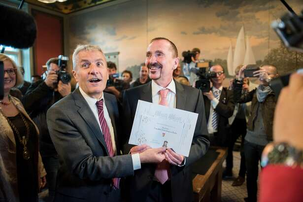 """BERLIN, GERMANY - OCTOBER 01:  Karl Kreile (right) and Bodo Mende cheer after their wedding at Schoeneberg district townhall on October 1, 2017 in Berlin, Germany. It was the very first wedding after new law """"Ehe fuer alle"""" (wedding for everyone) in Germany. Kreile and Mende  met each other in 1979 and lived in a same-sex union since 2002. (Photo by Steffi Loos/Getty Images)"""