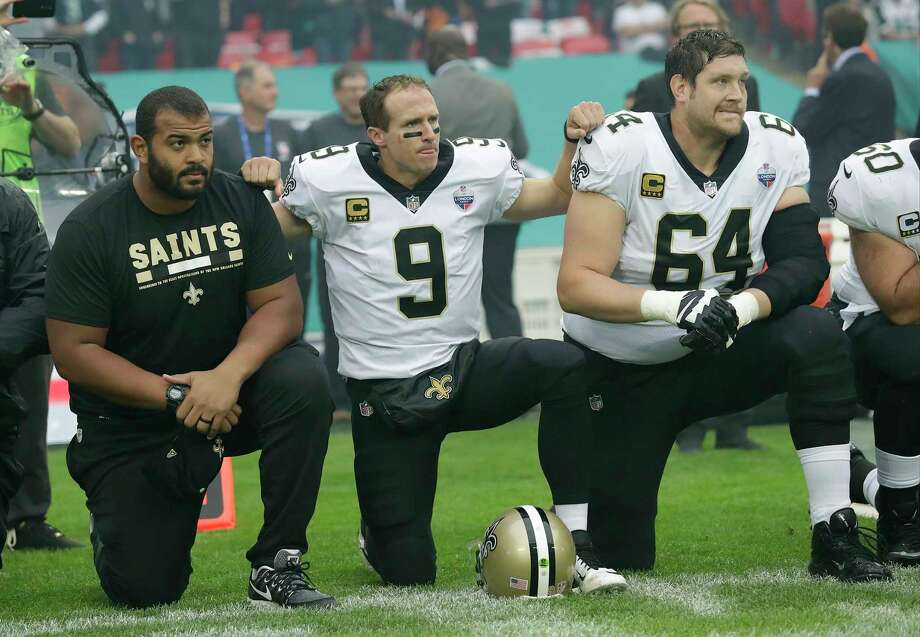 0e40b8edc New Orleans Saints quarterback Drew Brees (9) kneels down with teammates  before the U.S.