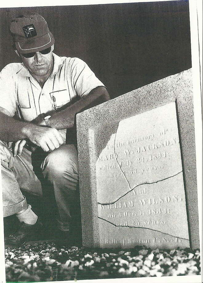 A Shell worker views a tombstone of two early settlers that was found on company property and later carefully moved to Heritage Park.