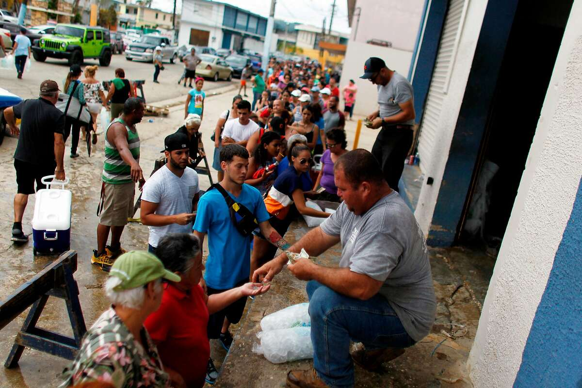 People wait in line to buy ice Saturday in Arecibo, Puerto Rico. The Trump administration says more than 10,000 federal officials are providing aid.