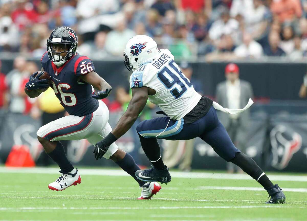 Houston Texans running back Lamar Miller (26) runs the ball against Tennessee Titans outside linebacker Brian Orakpo (98) during the second quarter of an NFL football game at NRG Stadium, Sunday, Oct. 1, 2017, in Houston.