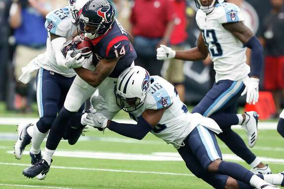 Houston Texans wide receiver Chris Thompson (14) is tackled by Tennessee Titans cornerback Brice McCain (23) and Tennessee Titans cornerback LeShaun Sims (36) on a long kick return during the second quarter of an NFL football game at NRG Stadium on Sunday, Oct. 1, 2017, in Houston.