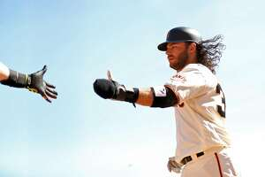 San Francisco Giants' Brandon Crawford slaps hands with Hunter pence after scoring on Nick Hundley's fielder's choice in 4th inning against San Diego Padres during MLB game at AT&T Park in San Francisco, Calif., on Sunday, October 1, 2017.