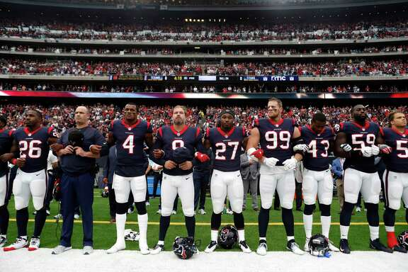 Houston Texans players lock arms as they stand for the National Anthem before an NFL football game against the Tennessee Titans at NRG Stadium on Sunday, Oct. 1, 2017, in Houston.