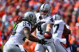 DENVER, CO - OCTOBER 1:  Quarterback Derek Carr #4  hands off to running back Marshawn Lynch #24 of the Oakland Raiders in the first quarter of a game against the Denver Broncos at Sports Authority Field at Mile High on October 1, 2017 in Denver, Colorado. (Photo by Dustin Bradford/Getty Images)