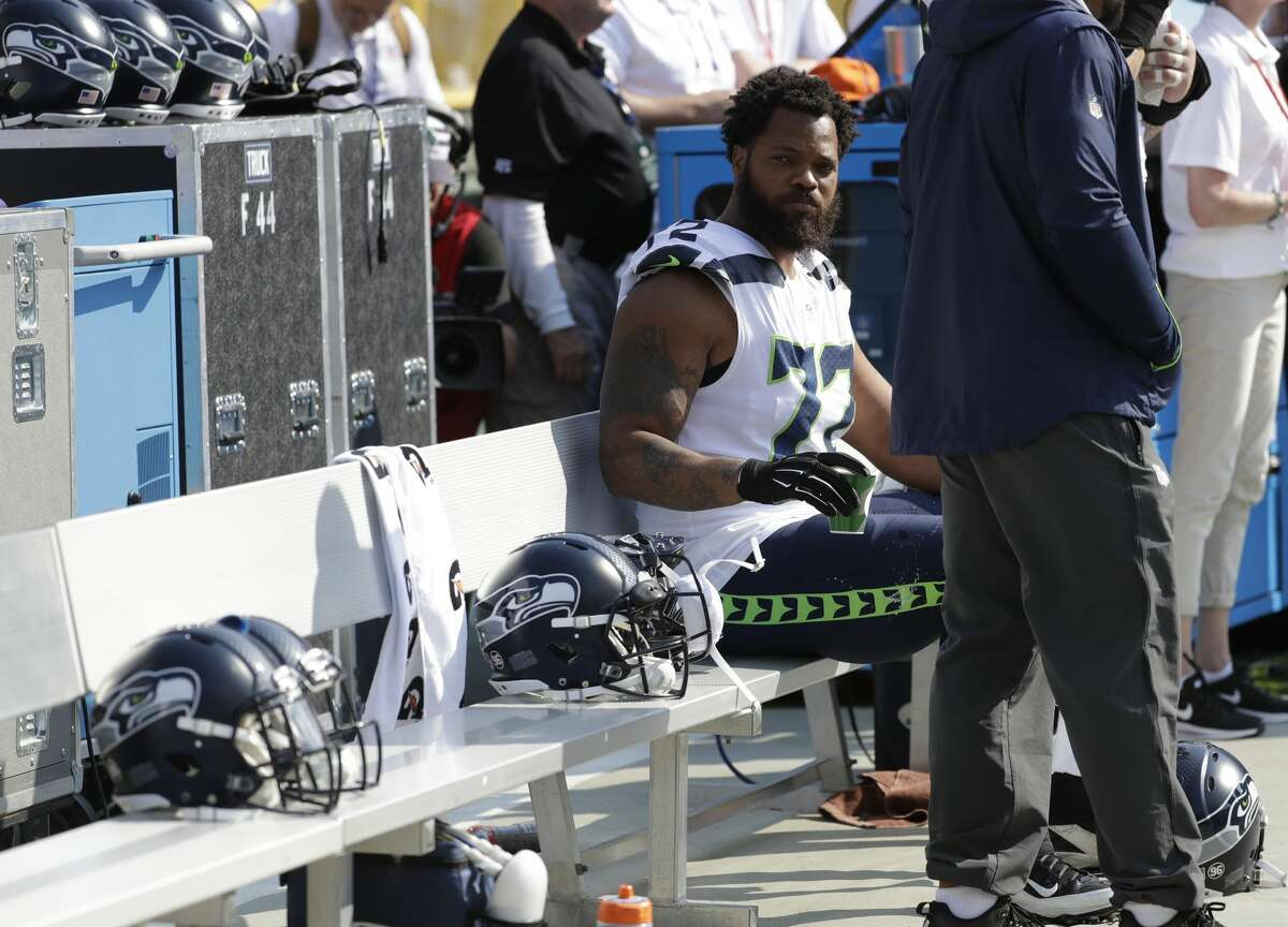 Seattle Seahawks' Michael Bennett remains seated on the bench during the national anthem before an NFL football game against the Green Bay Packers Sunday, Sept. 10, 2017, in Green Bay, Wis. (AP Photo/Morry Gash)