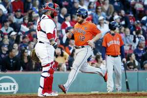 Houston Astros' Max Stassi (12) scores in front of Boston Red Sox's Sandy Leon on a single by Juan Centeno during the seventh inning of a baseball game in Boston, Sunday, Oct. 1, 2017. (AP Photo/Michael Dwyer)