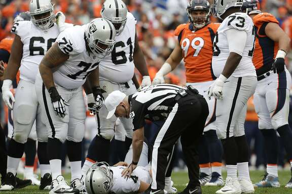 Oakland Raiders quarterback Derek Carr lays the field after being injured during the second half of an NFL football game against the Denver Broncos Sunday, Oct. 1, 2017, in Denver. (AP Photo/Joe Mahoney)