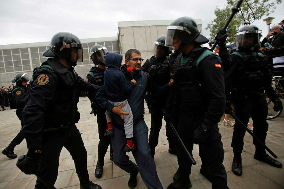 Civil guards force a man with a child to leave the entrance of a sports center, assigned to be a referendum polling station by the Catalan government in Sant Julia de Ramis, near Girona, Spain, Sunday, Oct. 1, 2017. Scuffles have erupted as voters protested as dozens of anti-rioting police broke into a polling station where the regional leader was expected to show up for voting on Sunday. (AP Photo/Francisco Seco) Photo: Francisco Seco, STR / Copyright 2017 The Associated Press. All rights reserved.