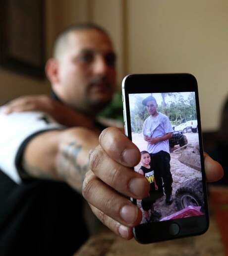 Lewis Solis shows a photo of his younger brother, Nick, and Nick's 6-year-old son. Nick Solis died in August as the Harris County Sheriff's SWAT team served a search warrant. Photo: Godofredo A. Vasquez, Houston Chronicle / Godofredo A. Vasquez