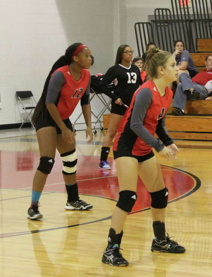 Coldspring-Oakhurst Lady Trojans Ja'Kayla Glaze (12) and Malin Patrick (4) prepare to play defense against the Anderson-Shiro Lady Owls during their Sept. 26 volleyball game. Photo: Jacob McAdams