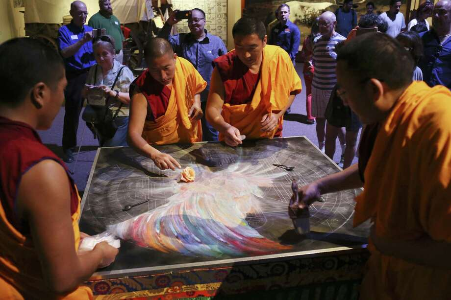 Buddhist monks from the Drepung Loseling Monastery gather the sand from a mandala painting during a Closing Ceremony at the Institute of Texan Cultures, Sunday, Oct. 1, 2017. The monks started creating the sand painting on Thursday and ended with the dispersing of the sand into the San Antonio River Sunday afternoon. Photo: JERRY LARA / San Antonio Express-News / San Antonio Express-News