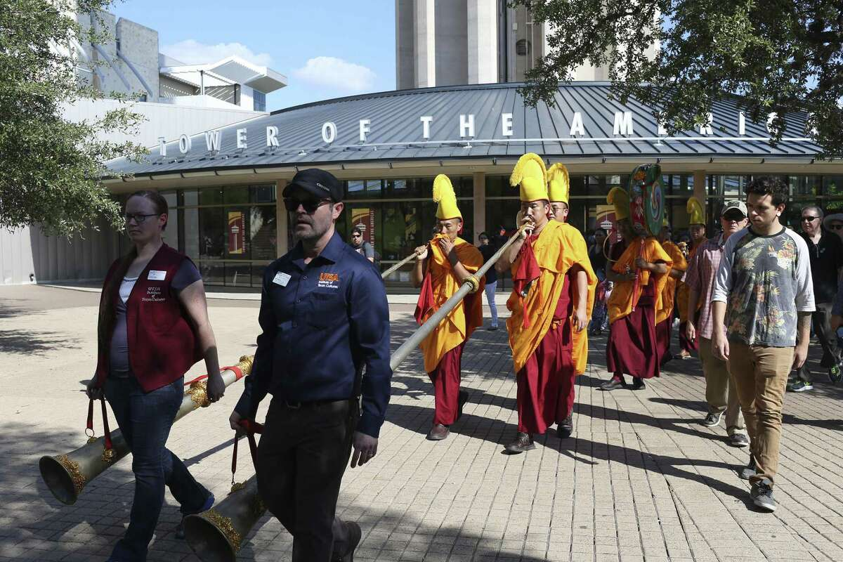 People join Buddhist monks from the Drepung Loseling Monastery in a sand mandala painting Closing Ceremony procession by the Tower of the Americas, Sunday, Oct. 1, 2017. The monks started creating the mandala sand painting on Thursday at the Institute of Texan Cultures and ended with the dispersing of the sand into the San Antonio River Sunday afternoon.
