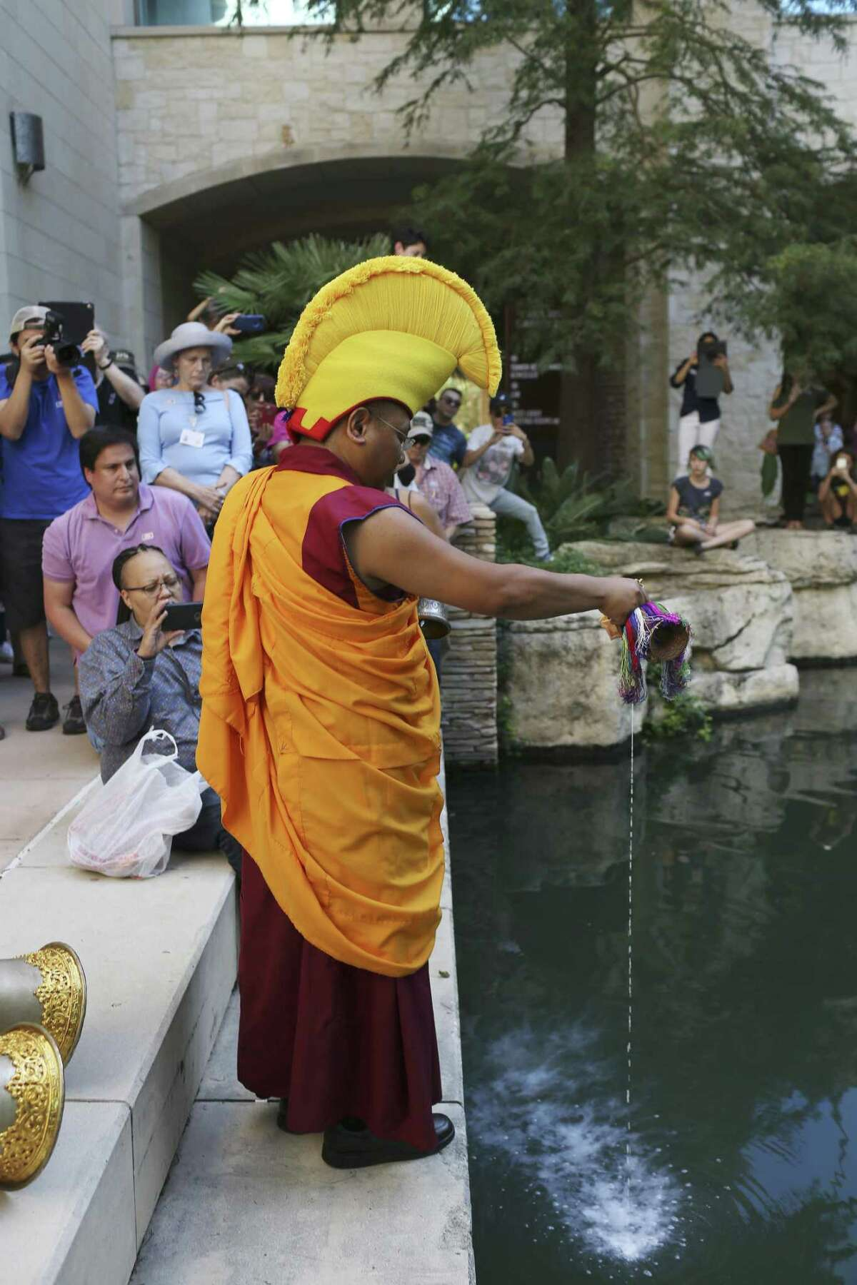 A Buddhist monk from the Drepung Loseling Monastery disperses sand from a mandala into the San Antonio River during a Closing Ceremony, Sunday, Oct. 1, 2017. The monks started creating the mandala sand painting at the Institute of Texan Cultures on Thursday and ended with the dispersing of the sand Sunday afternoon.