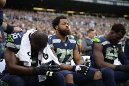 Seahawks players (l to r) Cliff Avril, Michael Bennett, and Frank Clark sit during the playing of the national anthem before Seattle's game versus the Indianapolis Colts at CenturyLink Field on Sunday, Oct. 1, 2017.