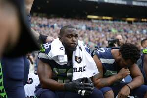Seahawks players Cliff Avril (left) and Michael Bennett sit before Seattle's game versus the Indianapolis Colts at CenturyLink Field on Sunday, Oct. 1, 2017.