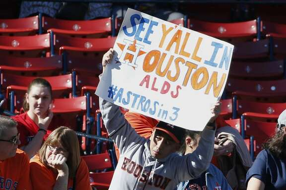 A Houston Astros fan holds a sign before a baseball game against the Boston Red Sox in Boston, Sunday, Oct. 1, 2017. (AP Photo/Michael Dwyer)