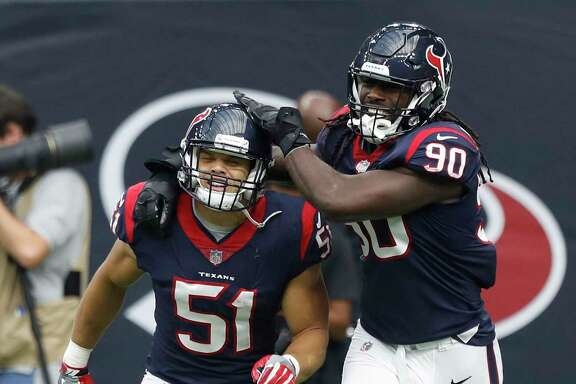The Texans' Dylan Cole (51) celebrates his fourth-quarter  touchdown off a 25-yard interception return with fellow linebacker Jadeveon Clowney.