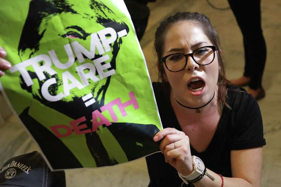 """WASHINGTON, DC - JULY 10:  A demonstrater from Arizona chants, """"Kill the bill or lose your job"""" while sitting on the floor outside the offices of Sen. Jeff Flake (R-AZ) during a protest against health care reform legislation in the Russell Senate Office Building on Capitol Hill July 10, 2017 in Washington, DC. More than 100 people from across the country were arrested during the protest that was organized by Housing Works and Center for Popular Democracy.  (Photo by Chip Somodevilla/Getty Images) ORG XMIT: 775004661 Photo: Chip Somodevilla / 2017 Getty Images"""