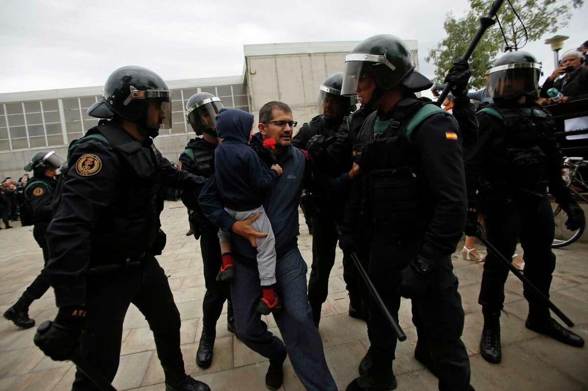 Civil guards force a man with a child to leave the entrance of a sports center, assigned to be a referendum polling station by the Catalan government in Sant Julia de Ramis, near Girona, Spain, Sunday, Oct. 1, 2017. Scuffles have erupted as voters protested as dozens of anti-rioting police broke into a polling station where the regional leader was expected to show up for voting on Sunday. (AP Photo/Francisco Seco) ORG XMIT: PW114
