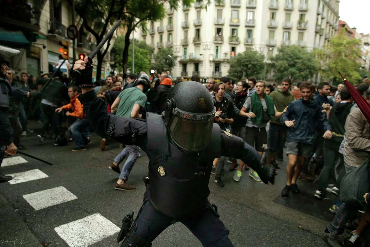 Spanish riot police swings a club against would-be voters near a school assigned to be a polling station by the Catalan government in Barcelona, Spain, Sunday, Oct. 1, 2017. Spanish riot police have forcefully removed a few hundred would-be voters from several polling stations in Barcelona. (AP Photo/Manu Fernandez) ORG XMIT: BCEM140