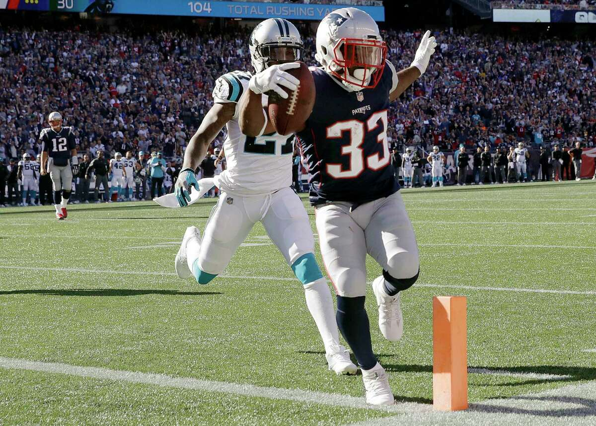 New England Patriots running back Dion Lewis (33) scores a touchdown in front of Carolina Panthers cornerback Kevon Seymour during the second half of an NFL football game, Sunday, Oct. 1, 2017, in Foxborough, Mass. (AP Photo/Charles Krupa) ORG XMIT: FBO133