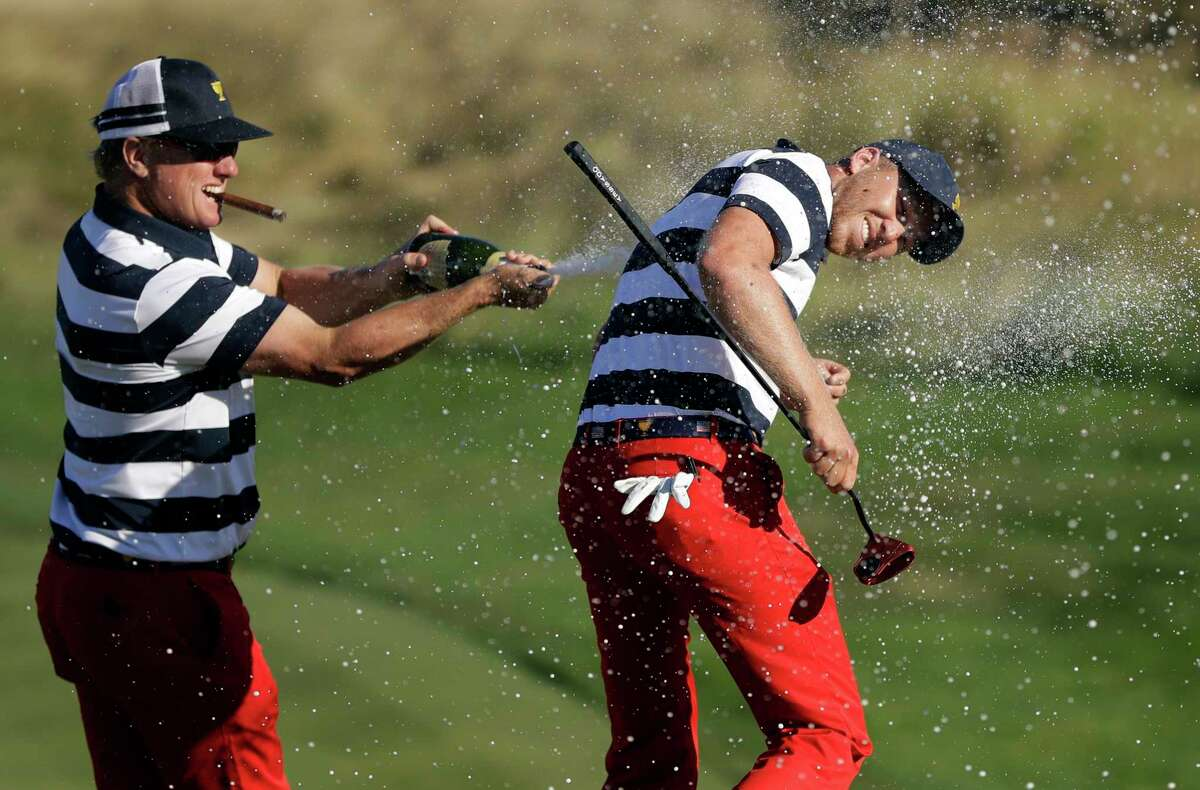U.S. Team member Charley Hoffman, left, douses teammate Daniel Berger after he won the final round of the Presidents Cup golf tournament at Liberty National Golf Club in Jersey City, N.J., Sunday, Oct. 1, 2017. (AP Photo/Julio Cortez) ORG XMIT: NYRD154
