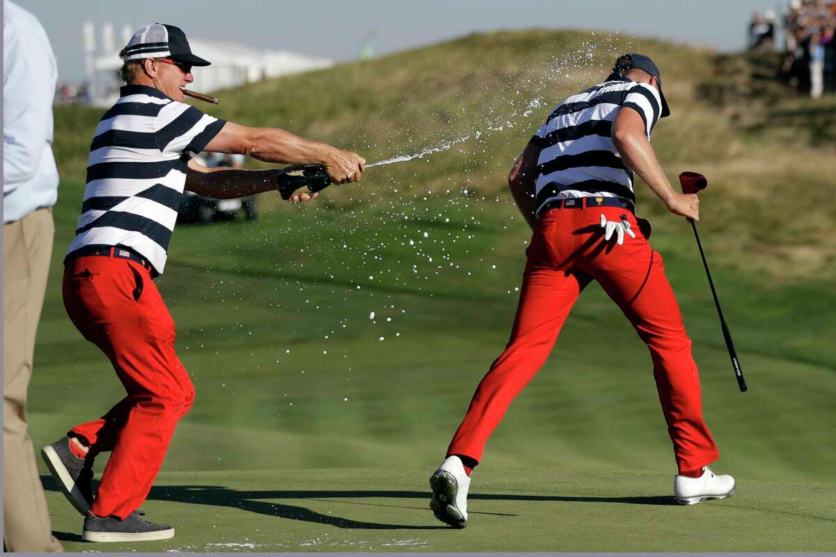 U.S. Team member Charley Hoffman, left, douses teammate Daniel Berger after he won the final round of the Presidents Cup golf tournament at Liberty National Golf Club in Jersey City, N.J., Sunday, Oct. 1, 2017. (AP Photo/Julio Cortez) ORG XMIT: NYRD153