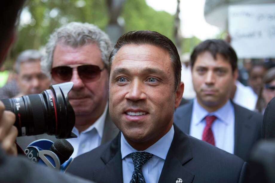 FILE- In this July 17, 2015 file photo, former U.S. Rep. Michael Grimm, center, leaves following his sentencing at federal court in the Brooklyn borough of New York. Grimm, who went to prison for tax fraud and once threatened to throw a TV reporter off a balcony, is set to announce Sunday, Oct. 1, 2017, that he will try to reclaim his old seat in Congress. (AP Photo/Kevin Hagen, File) ORG XMIT: NYR403 Photo: Kevin Hagen / FR170574 AP