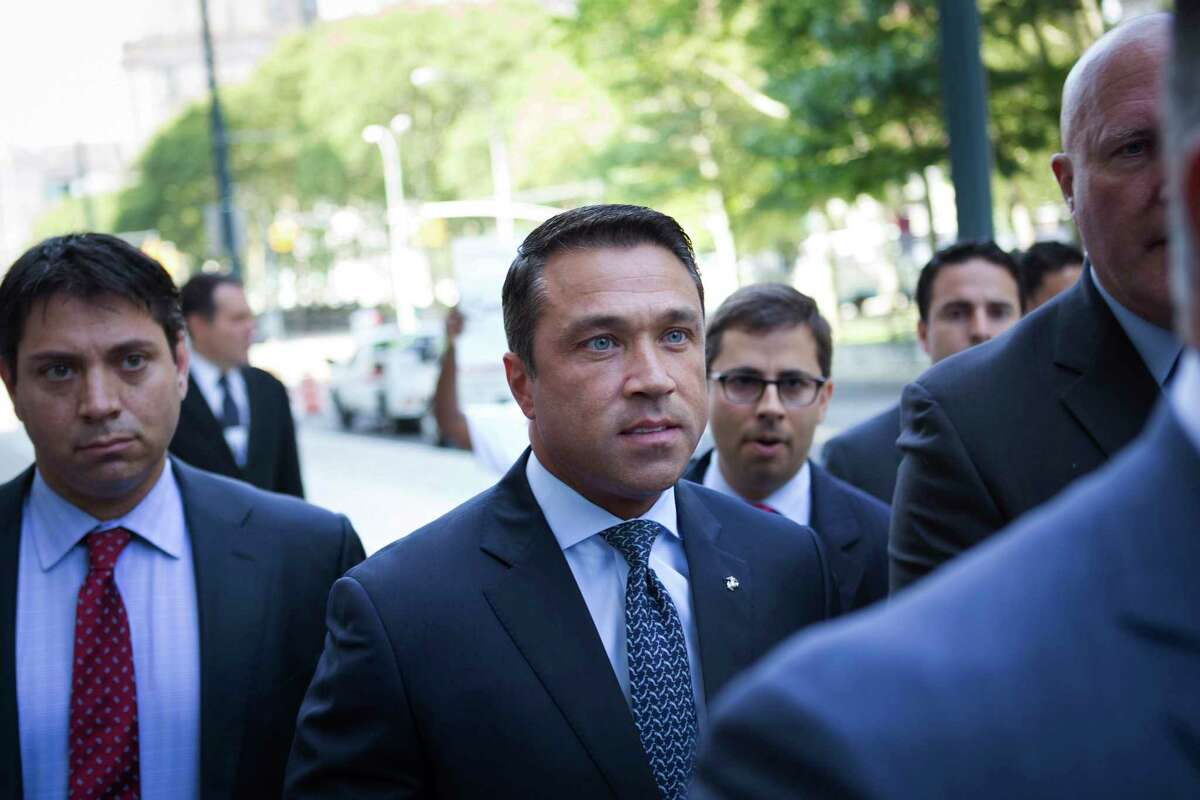 FILE- In this July 17, 2015 file photo, former U.S. Rep. Michael Grimm, center, arrives ahead of his sentencing at federal court in the Brooklyn borough of New York. Grimm, who went to prison for tax fraud and once threatened to throw a TV reporter off a balcony, is set to announce Sunday, Oct. 1, 2017, that he will try to reclaim his old seat in Congress. (AP Photo/Kevin Hagen, File) ORG XMIT: NYR402