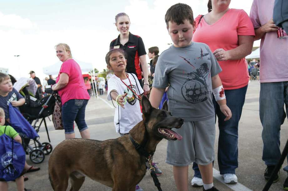 Skylar Helms, 8, right, and Emily Paz, 7, pet Conroe ISD police dog Bronco during the National Night Out event on Oct. 4, 2016, at the Target parking lot in Conroe. Photo: Michael Minasi, Photographer / Internal
