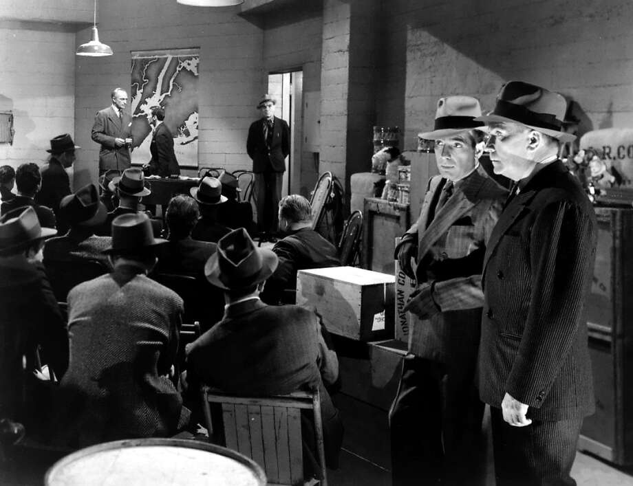 """Humphrey Bogart and William Demarest crash a meeting of Nazis led by Conrad Veidt (background) in """"All Through the Night"""" (1942). Photo: Warner Bros., 1942"""