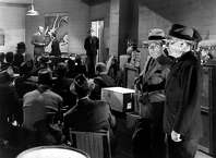 """Hunphrey Bogart and William Demarest crash a meeting of Nazis led by Conrad Veidt (background) in """"All Through the Night"""" (1942)."""