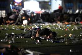 LAS VEGAS, NV - OCTOBER 01: (EDITORS NOTE: Image contains graphic content.) A person lies on the ground at the Route 91 Harvest country music festival after apparent gun fire was heard on October 1, 2017 in Las Vegas, Nevada. There are reports of an active shooter around the Mandalay Bay Resort and Casino.  (Photo by David Becker/Getty Images)