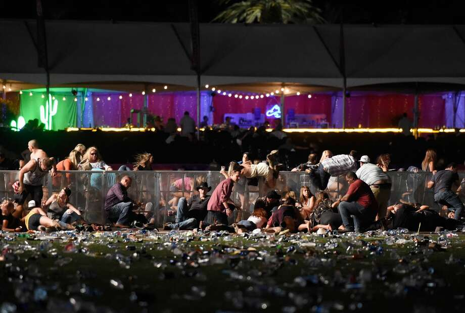 LAS VEGAS, NV - OCTOBER 01:  People dive for cover at Route 91 Harvest country music festival after apparent gun fire was heard on October 1, 2017 in Las Vegas, Nevada.  There are reports of an active shooter around the Mandalay Bay Resort and Casino.  (Photo by David Becker/Getty Images) Photo: David Becker/Getty Images