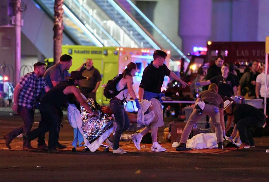 An injured person is tended to in the intersection of Tropicana Ave. and Las Vegas Boulevard after a mass shooting at a country music festival nearby on October 2, 2017 in Las Vegas, Nevada. A gunman has opened fire on a music festival in Las Vegas, killing over 20 people. Police have confirmed that one suspect has been shot dead. The investigation is ongoing. (Photo by Ethan Miller/Getty Images) Photo: Ethan Miller/Getty Images