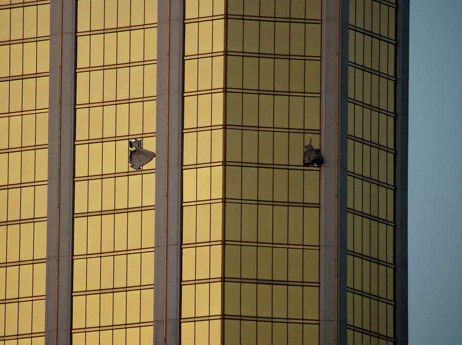 Drapes billow out of broken windows at the Mandalay Bay resort and casino Monday, Oct. 2, 2017, on the Las Vegas Strip following a deadly shooting at a music festival in Las Vegas. A gunman was found dead inside a hotel room. Photo: John Locher, AP / Copyright 2017 The Associated Press. All rights reserved.