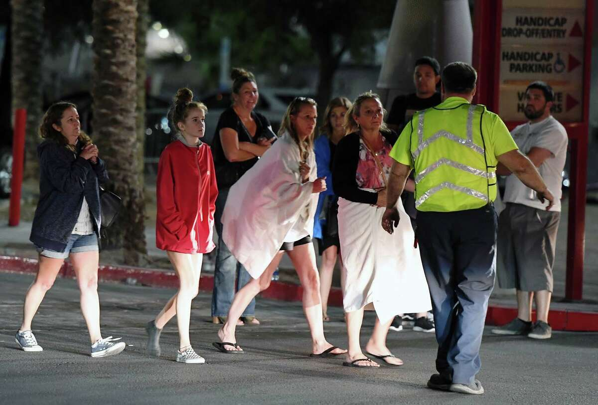 People are directed to rides outside the Thomas & Mack Center after a mass shooting at a country music festival on October 2, 2017 in Las Vegas, Nevada. People who could not go to hotel-casinos that were closed after the shooting are temporarily staying at the center. The gunman, identified as Stephen Paddock, 64, of Mesquite, Nevada, opened fire from the Mandalay Bay Resort and Casino on the music festival, leaving at least 50 people dead and hundreds injured.