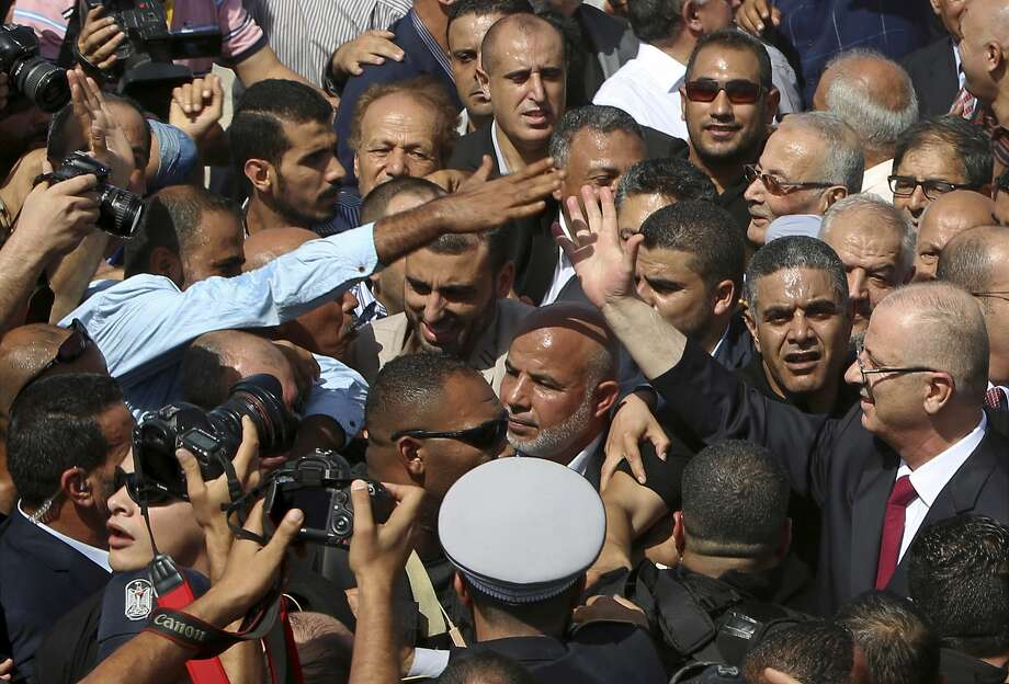 Palestinian Prime Minister Rami Hamdallah, reaches out to shake hands with a supporter on his arrival to the Palestinian side of the Beit Hanoun border crossing in the northern Gaza Strip, Monday, Oct. 2, 2017. Hamdallah is in Gaza for the most ambitious attempt yet to end the 10-year rift between rival Palestinian factions Fatah and Hamas. (AP Photo/Adel Hana) Photo: Adel Hana, Associated Press