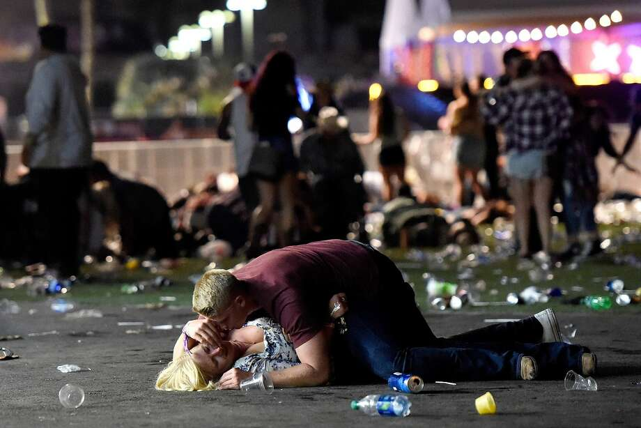 A man lays on top of a woman as others flee the Route 91 Harvest country music festival grounds after a active shooter was reported on October 1, 2017 in Las Vegas, Nevada. A gunman has opened fire on a music festival in Las Vegas, leaving at least 2 people dead. Police have confirmed that one suspect has been shot. The investigation is ongoing. Photo: David Becker, Getty Images